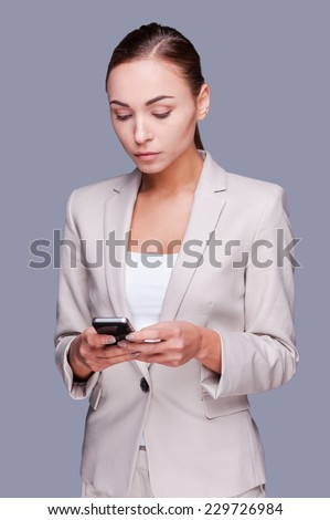 Businesswoman with mobile phone. Confident young businesswoman holding mobile phone while standing against grey background  - stock photo