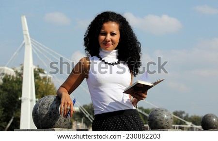 Businesswoman with notebook and pen at the street on sky background