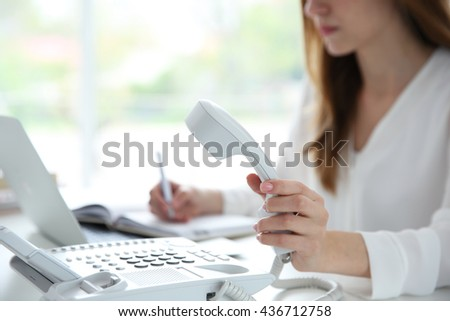 Businesswoman with office IP telephone - stock photo