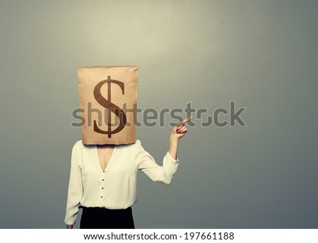 businesswoman with paper bag on her head pointing at empty grey copyspace - stock photo