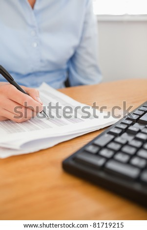 businesswoman with pen going through numbers in her office