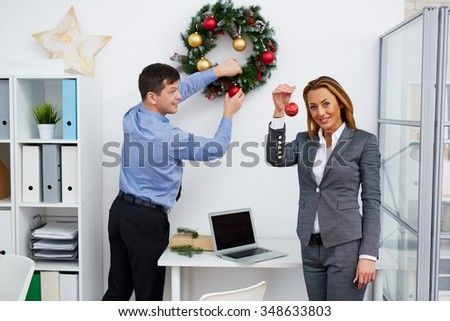 Businesswoman with red bubble looking at camera while her colleague decorating office Christmas wreath