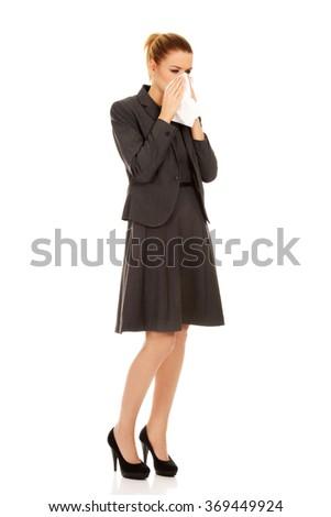 Businesswoman with sneezing into tissue. - stock photo