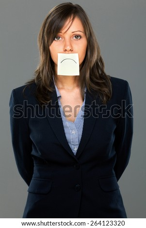 Businesswoman with sticky note on gray background