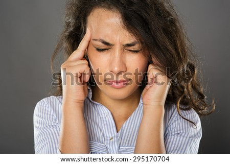 Businesswoman with strong migraine, closeup over gray background - stock photo