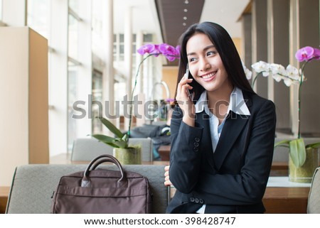 Businesswoman with suitcase calling with mobile phone.