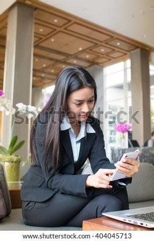 Businesswoman with suitcase playing mobile phone in the hotel lobby.