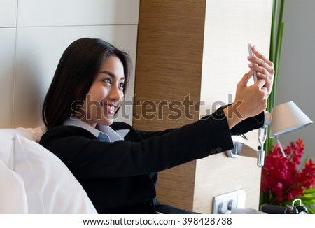 Businesswoman with suitcase playing mobile phone on the bed in the hotel.