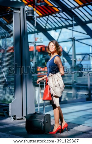 Businesswoman with suitcase standing at the bus station of Amsterdam
