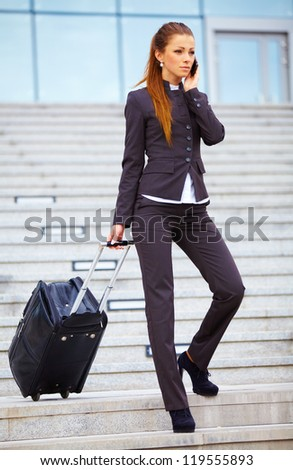 Businesswoman with suitcase using mobile and waiting