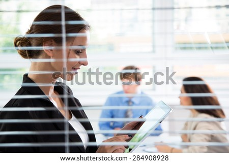 Businesswoman with tablet computer with colleagues on background - stock photo