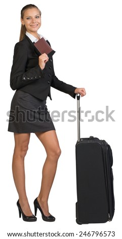Businesswoman with wheeled travel bag, showing passport with blank cover, looking at camera. Isolated over white background