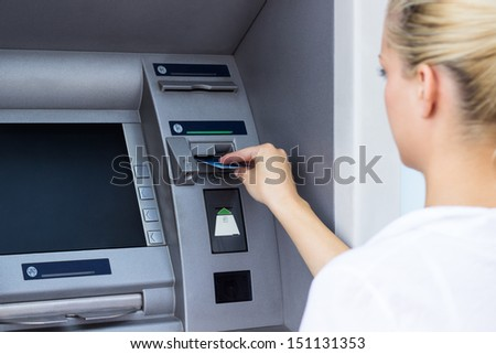 Businesswoman withdrawing money from credit card at ATM