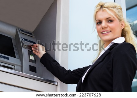 Businesswoman withdrawing money from credit card at ATM, looking at camera - stock photo
