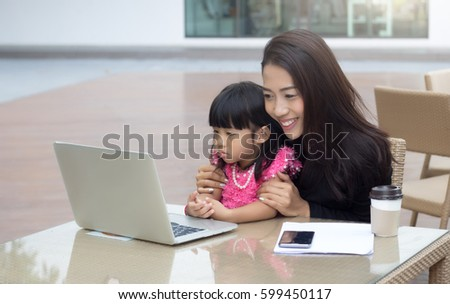 businesswoman work at home with her daughter with laptop