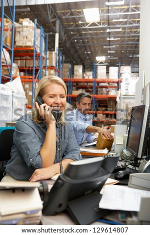 Businesswoman Working At Desk In Warehouse