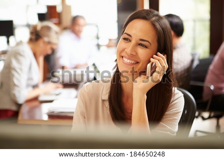 Businesswoman Working At Desk Using Mobile Phone - stock photo