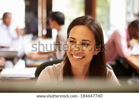 Businesswoman Working At Desk With Meeting In Background - stock photo