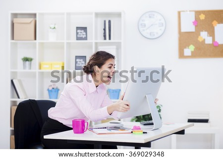 Businesswoman working at her desk,screaming in front on computer monitor. Shallow depth of field - stock photo
