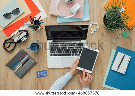 Businesswoman working at office desk with a laptop and a digital tablet, she is shopping with a credit card, top view