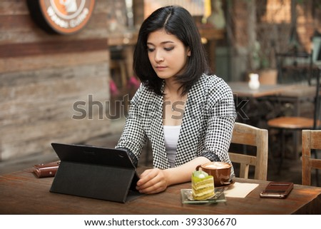 Businesswoman working in a coffee shop by using tablet.