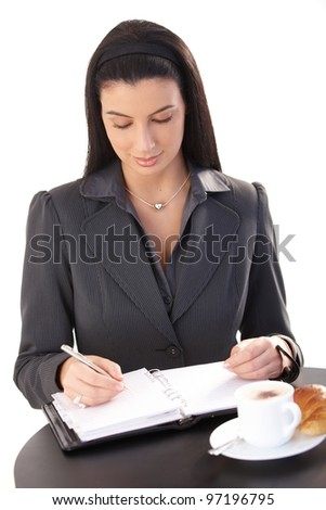 Businesswoman working in cafe during breakfast croissant and cappuccino, taking notes to personal organizer.?