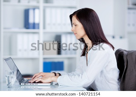 Businesswoman working in front of her laptop in a side view shot - stock photo