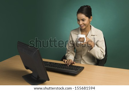 Businesswoman working in office with cup of coffee
