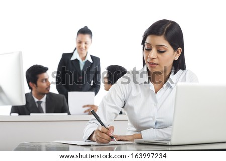 Businesswoman working in the office with her colleagues in the background