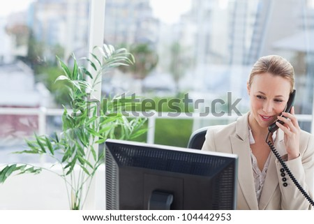 Businesswoman working on a computer with city view in background