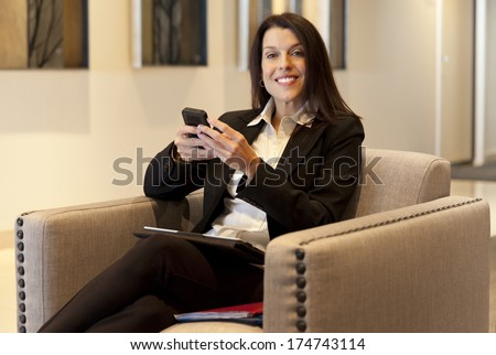 Businesswoman working on cellphone at the hotel - stock photo