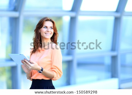 Businesswoman working on digital tablet outdoor over building background - stock photo