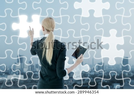 Businesswoman working on digital virtual screen of jigsaw, business strategy concept - stock photo