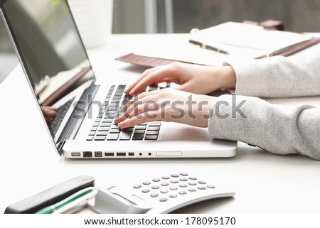 Businesswoman working on laptop and calculating data - stock photo