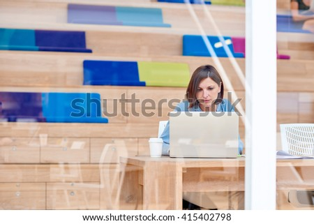 Businesswoman working on laptop in colourful creative space - stock photo