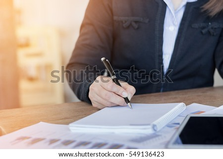 Businesswoman working on office desk, Watching something on computer laptop. He was thinking about something for idea and make a Note something of Idea, Blurred background, Business concept.