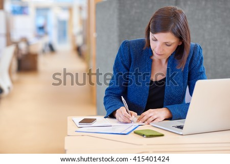 Businesswoman working on paperwork at her desk in shared office - stock photo