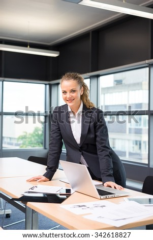 Businesswoman working & sitting at her desk in an office