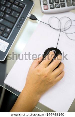 Businesswoman working with laptop and mouse - stock photo