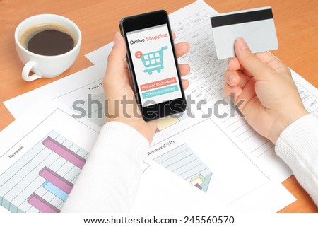 Businesswoman works at her workplace with smartphone, and credit card - stock photo