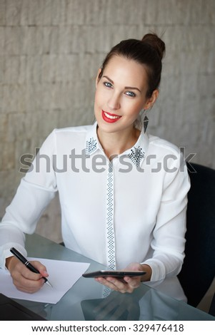 Businesswoman write on blank paper and holding tablet, teeth smile - stock photo