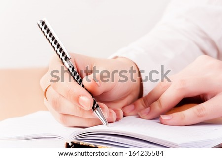 businesswoman writes mission for business plan in office - stock photo