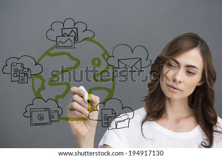 Businesswoman writing doodle against grey vignette - stock photo