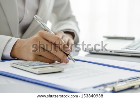 Businesswoman writing down on the document
