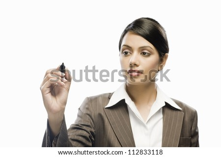 Businesswoman writing on a blank space against a white background - stock photo
