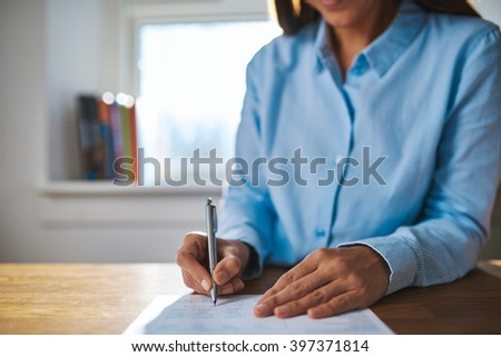 Businesswoman writing on a document as she sits at her desk in the office, close up view of her hands and the pen