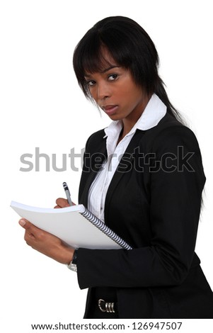 Businesswoman writing on clip-board