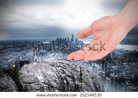 Businesswomans hand presenting against large rock overlooking huge city - stock photo