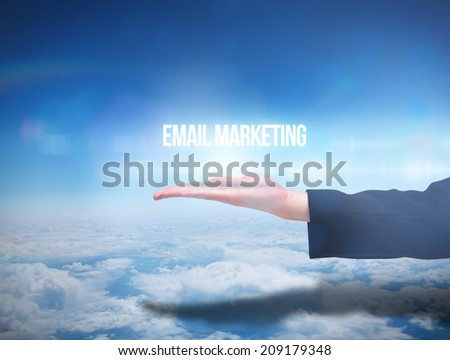 Businesswomans hand presenting email marketing against blue sky over clouds at high altitude - stock photo