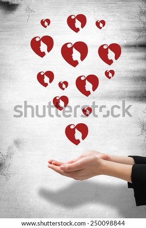 Businesswomans hands presenting against heart - stock photo